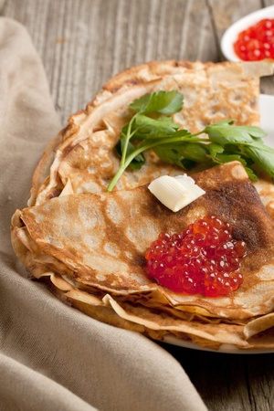 Red caviar with piece of butter and parsley on pancakes Stock Photo - 13134573