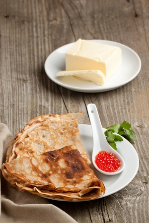 Plate of pancakes with red caviar and fresh butter served on old wooden table photo