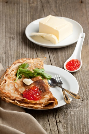 Plate of pancakes with red caviar and fresh butter served with tableware on old wooden table photo
