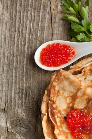 Tot view on pancakes with spoon of red caviar and twig of parsley served on old wooden background photo