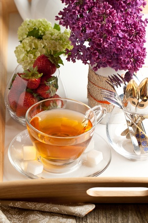 Breakfast with tea and fresh strawberries served on tray with lilac flowers and tablewere Stock Photo