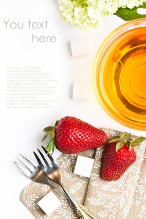 Top view on cup of tea and fresh strawberries with flowers and tableware over white  With sample text Stock Photo - 13542097