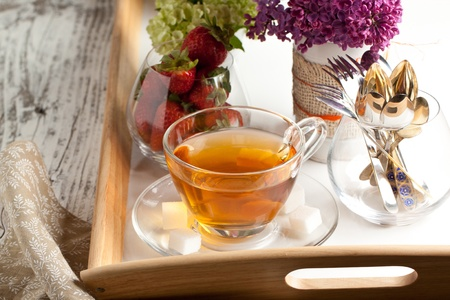 Breakfast with tea and fresh strawberries served on tray with lilac flowers and tableware photo