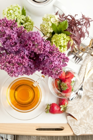 Top view on cup of tea and fresh strawberries with flowers and tableware served on white tray photo