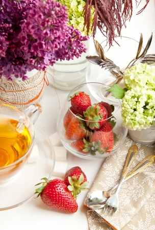 Breakfast with tea and fresh strawberries served with lilac flowers and tableware Stock Photo - 13653797