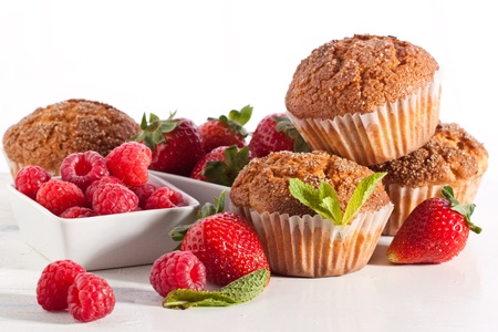 Homemade muffins with fresh strawberries and raspberries on white table Stock Photo - 13736230
