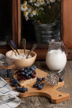 Homemade cake with fresh blueberries served on wooden table with jug of milk photo