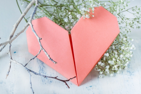 pink origami heart on white with blue wooden table with white flowers and painted branch  photo