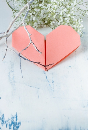pink origami heart on white wooden table with bunch of Gypsophila  Baby s-breath flowers  and branch  photo