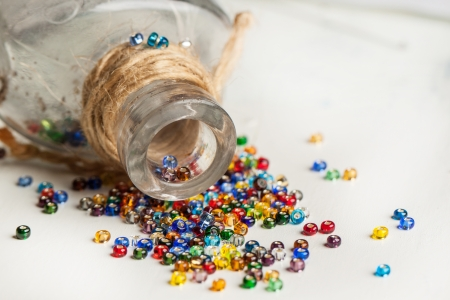 colorful beautiful glass beads withvintage glass bottle on white wooden table Stock Photo