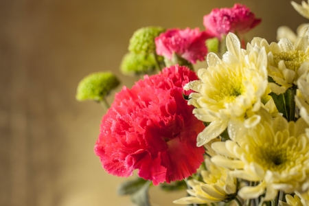 Bouquet of pink carnations and yellow chrysanthemum flowers on golden bokeh background photo