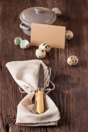 Easter table setting with quail eggs, card and vintage silverware on old wooden table  photo