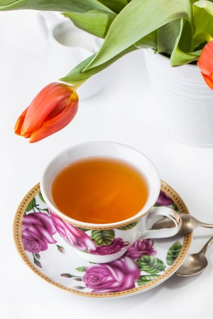 Beauty tea cup full of tea with bouquet of red tulips on white background  photo