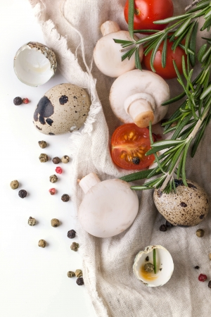 Top view on quail eggs with white mushrooms, sliced cherry tomatoes and rosemary on white rag over white photo