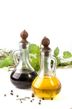 O azeite de oliva e vinagre em garrafas vintage, ervas e pimenta sobre o branco