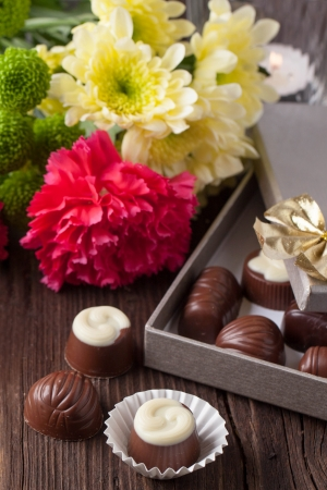 Chocolate candies, lightning candle and bouquet of carnation and chrysanthemum flowers on old wooden table photo