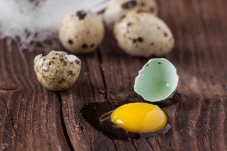 broken quail egg with the leaked yolk on old wooden table photo