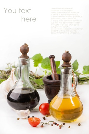Olive oil and vinegar in vintage bottles with garlic, sliced cherry tomatoes, mint and rosemary in wooden mortar with sample text  Stock Photo
