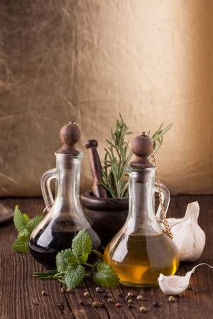 Olivenöl und Essig in vintage Flaschen auf alten Holztisch mit Knoblauch, Minze und Rosmarin in vintage Mörtel