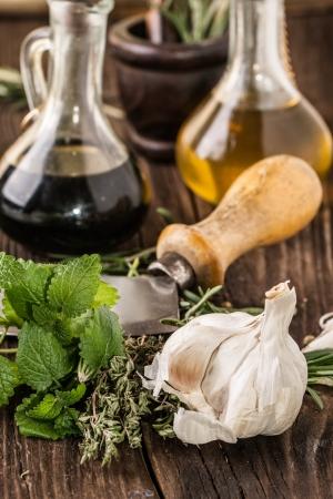 老式刀與大蒜,薄荷,百里香,油和醋的葡萄酒瓶上的舊木桌上