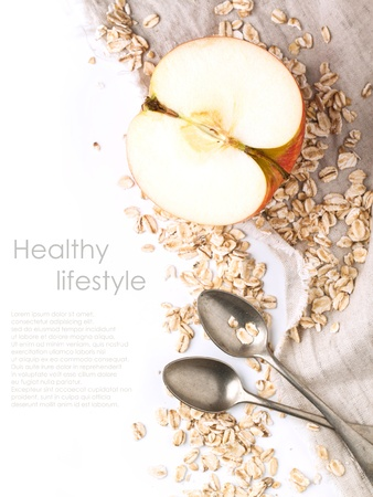 Top view on half apple with crops oatmeal and vintage spoons on textile over white with sample text Stock Photo - 17918071