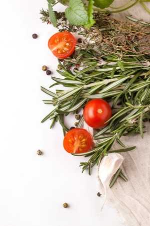 Top view on sliced tomatoes cherry with garlic, rosemary, thyme and melissa on white rag over white photo