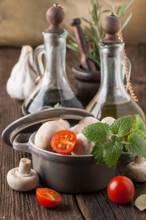 olive oil and vinegar in vintage bottles on wooden table with garlic, mint, mushrooms in ceramic pot and rosemary in vintage mortar photo