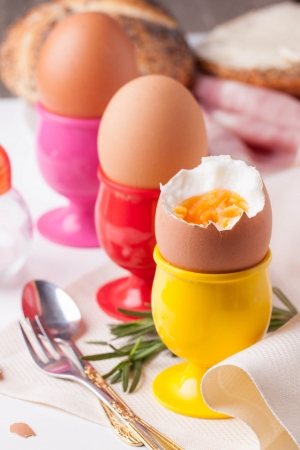peeled boiled eggs in colorful cups with rosemary, silverware, bread on white napkin Stock Photo - 18150507