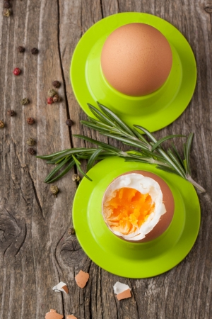 top view on peeled boiled eggs in green cups with rosemary on wooden table Stock Photo - 18150511