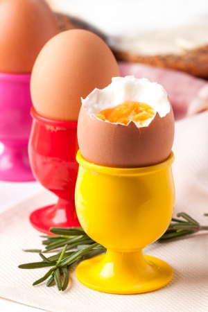 peeled boiled eggs in colorful cups with rosemary on white napkin Stock Photo - 18261331