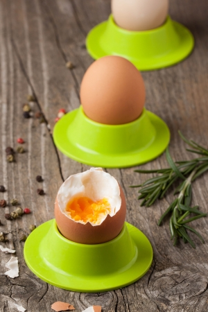 peeled boiled eggs in green cups with rosemary on wooden table Stock Photo - 18261342