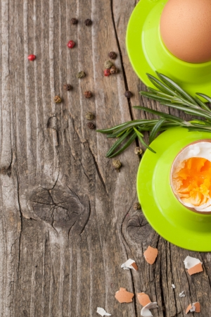 top view on peeled boiled eggs in green cups with rosemary on wooden table Stock Photo - 18261366