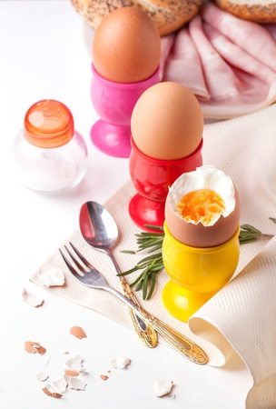 peeled boiled eggs in colorful cups on white table with salt in saltcellar, rosemary, silverware and bread with ham Stock Photo - 18558538