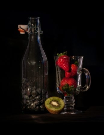 delicious berries on glass cup and bottle isolated over black   photo