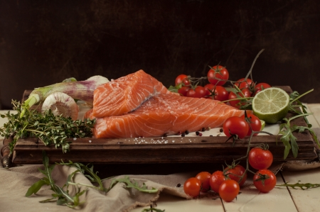 salted fresh salmon fish on vintage board with vegetables and spice photo