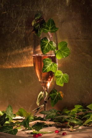 glass of pink champagne in vintage glass with leafs photo