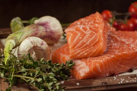 야채와 향신료와 함께 빈티지 보드에 소금 된 신선한 연어 물고기