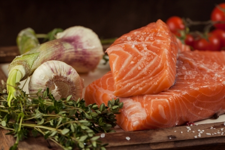 salted fresh salmon fish on vintage board with vegetables and spice Stock Photo