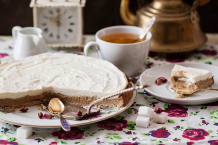 Cottage cheese tart on plate with cugar, tea, clocks and silverdishes photo