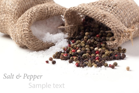 Salt and pepper scattered from sacks over white with sample text photo