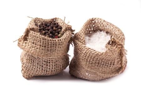 Tow sacks of salt and pepper over white photo