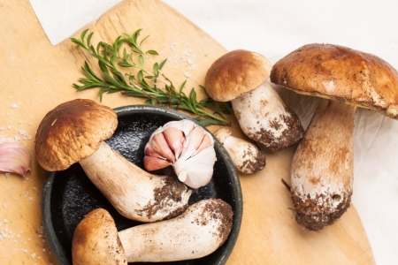 Top view on heap of cep mushrooms with thyme and garlic served on wooden cutting board photo