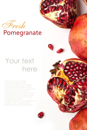 Top view on sliced and whole pomegranates over white with sample text