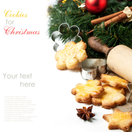 Homemade sugar cookies served with metal cookie cutters and anise near christmas tree over white with sample text photo