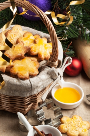 Basket of homemade sugar cookies served with metal cookie cutters and honey near christmas tree over tablecloth photo