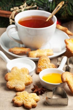 Tasse schwarzen Tee serviert mit hausgemachten Weihnachtszuckerplätzchen, Honig und Metall Ausstechformen über Tischdecke