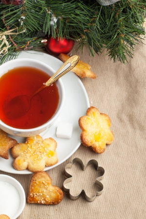 Cup of black tea served with homemade sugar cookies, honey and metal cookie cutters over tablecloth photo