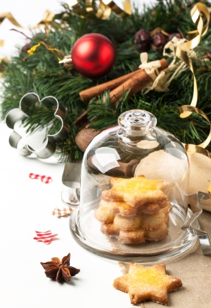 Homemade sugar cookies served in glass tray with cap near christmas tree over white photo