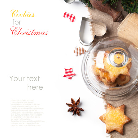 Top view on homemade sugar cookies served in glass tray with cap with anise and metal cookie cutters over white with sample text photo