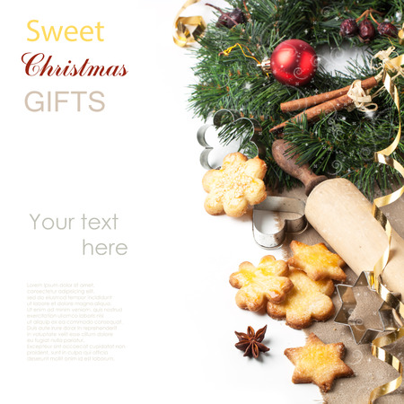 Homemade sugar cookies served with metal cookie cutters and wooden rolling pin near christmas wreath over white with sample text photo